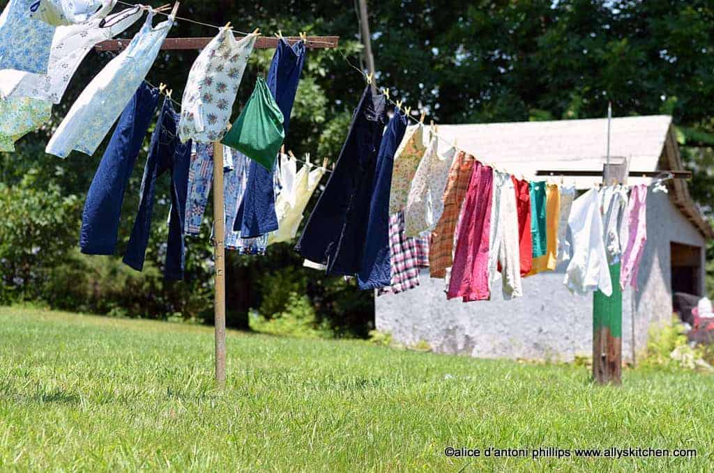 Various articles of clothing hanging from a clothesline with a white building in background